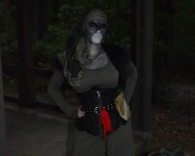Foto de uma mulher com maquiagem e roupas escuras se preparando para interpretar um NPC.