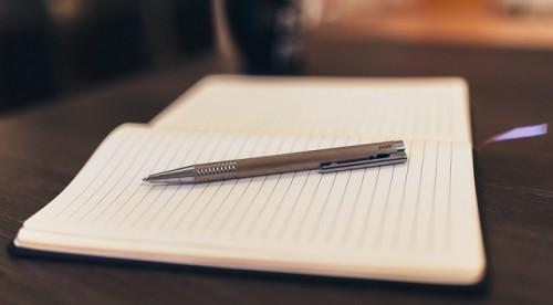 Um caderno aberto e uma caneta em cima.