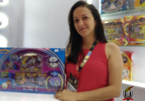 Uma mulher segurando um box de cartas Pokémon na Brasil Game Show.